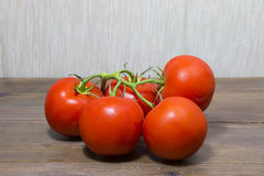 Tomatoes. Branch ripe tomatoes on wooden desk Stock Photography