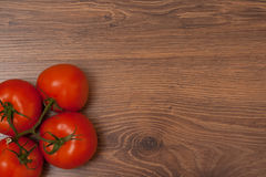 Tomatoes on the branch. Ripe tomatoes on the branch on the wooden table stock image