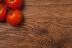 Tomatoes on the branch. Ripe tomatoes on the branch on the wooden table royalty free stock photography