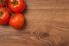 Tomatoes on the branch. Ripe tomatoes on the branch on the wooden table royalty free stock images