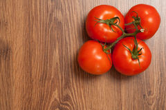 Tomatoes on the branch. Ripe tomatoes on the branch on the wooden table stock photos