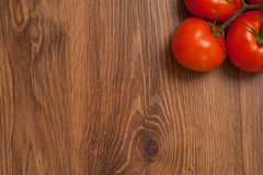 Tomatoes on the branch. Ripe tomatoes on the branch on the wooden table royalty free stock photo