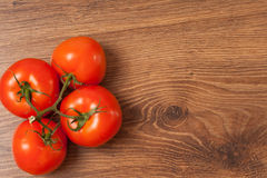 Tomatoes on the branch. Ripe tomatoes on the branch on the wooden table royalty free stock image