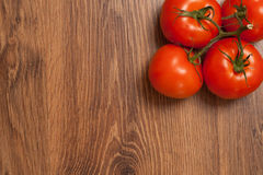 Tomatoes on the branch. Ripe tomatoes on the branch on the wooden table royalty free stock photos