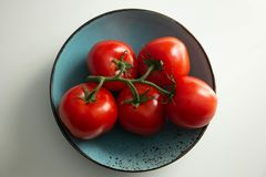 Tomatoes on a branch on a turquoise plate royalty free stock photos