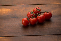 Tomatoes on brown textured wood Royalty Free Stock Image