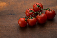 Tomatoes on brown textured wood Royalty Free Stock Photo