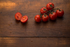 Tomatoes on brown textured wood Royalty Free Stock Photography