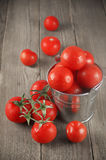 Tomatoes in bucket. Whole wet tomatoes in galvanized bucket on rustic wooden table Stock Photography