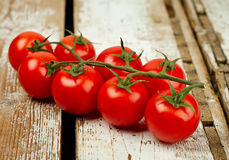 Tomatoes bunch. Closeup on wooden table Royalty Free Stock Photo