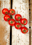 Tomatoes bunch. Closeup on wooden table Stock Photo