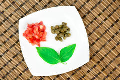 Tomatoes, capers and basil on a white plate Stock Images
