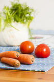 Tomatoes, carrots and fennel on blue tablecloth Royalty Free Stock Photos