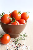 Tomatoes in a ceramic plate. On a wooden surface Stock Photography