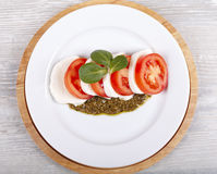Tomatoes, cheese mozzarella and pesto sauce top view. Fresh salad from tomatoes with cheese a mozzarella and pesto sautse Royalty Free Stock Images