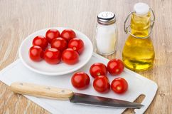 Tomatoes cherry in saucer, on cutting board, vegetable oil, knif Royalty Free Stock Image