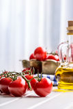 Tomatoes. Cherry tomatoes. Cocktail tomatoes. Fresh grape tomatoes carafe with olive oil Royalty Free Stock Images