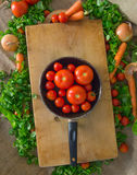 Tomatoes, cherry tomatoes, salad, carrots, pan on a wooden surface Stock Photo