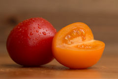 Tomatoes. Closeup of one red and one orange tomato on wooden table Stock Photography