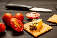 Tomatoes, cookies and blue cheese on a black wooden rustic board. Dark food stock photography
