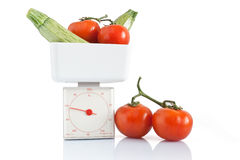 Tomatoes and courgettes on balance Stock Photo