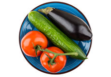 Tomatoes, cucumber and eggplant in blue plate on white Stock Photography