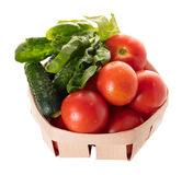 Tomatoes with cucumber and spinach leaves in a basket Royalty Free Stock Photos