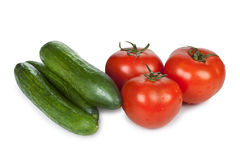 Tomatoes and cucumbers. Fresh vegetables, delicious tomatoes and cucumbers isolated on a white background Royalty Free Stock Photo