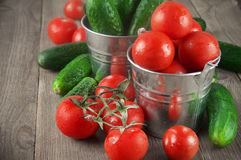 Tomatoes and cucumbers in buckets. Whole wet tomatoes and cucumbers in galvanized buckets on rustic wooden table Stock Photos