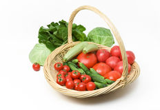 Tomatoes Cucumbers Cabbage Basket. A basket full of tomatoes and cucumbers with some cabbage behind it Royalty Free Stock Images