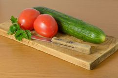 Tomatoes and cucumbers on the cutting board. Tomatoes and cucumbers and a knife lying on the board Royalty Free Stock Photos