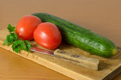 Tomatoes and cucumbers on the cutting board. Tomatoes and cucumbers and a knife lying on the board Royalty Free Stock Photography