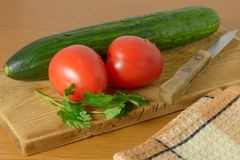 Tomatoes and cucumbers on the cutting board. Tomatoes and cucumbers and a knife lying on the board Royalty Free Stock Images