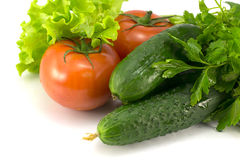 TOmatoes, cucumbers and greens. Omatoes, cucumbers and greens on a white background Royalty Free Stock Image