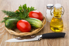 Tomatoes, cucumbers and greens in wicker basket, vegetable oil, Stock Photo