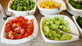Tomatoes, cucumbers ,lemon slices   in bowls  in a restaurant Stock Image