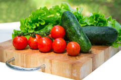 Tomatoes, cucumbers, lettuce. Leaves on a tray made of wood. Fresh fruits, closeup Stock Photos