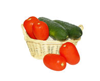 Tomatoes and cucumbers. Light a small wicker basket with tomatoes and cucumbers. Basket and vegetables isolated on a white background Royalty Free Stock Photography