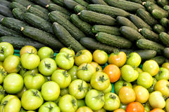 Tomatoes and cucumbers. Many tomatoes and cucumbers on display in a supermarket Royalty Free Stock Image