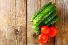 Tomatoes and cucumbers on an old wooden table. Tomatoes and cucumbers on an old wooden table Stock Images