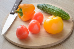 Tomatoes and cucumbers and peppers on a cutting board. Royalty Free Stock Image