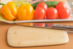 Tomatoes and cucumbers and peppers cutting board on the table. Royalty Free Stock Photography