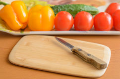 Tomatoes and cucumbers and peppers cutting board on the table. Stock Photo