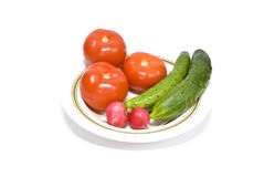 Tomatoes cucumbers and radishes. Three tomatoes, two cucumbers and two radishes on a plate, isolated on white background stock image