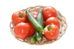 Tomatoes and Cucumbers. Red Tomatoes and Cucumbers in a Bowl Isolated on White Background Royalty Free Stock Images