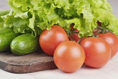 Tomatoes, cucumbers and salad on cutting board Stock Photography
