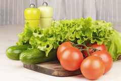 Tomatoes, cucumbers and salad on cutting board Royalty Free Stock Images