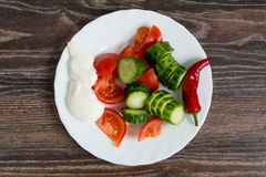 Tomatoes and cucumbers salad in plate. On wooden background Royalty Free Stock Images