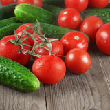 Tomatoes and cucumbers on wood Stock Images