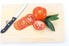 Tomatoes. Cut by a kitchen knife on a wooden board Royalty Free Stock Photography